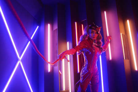 Sexy young woman in leather red dress with cat mask in neon lights with the whip
