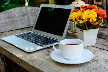 a cup of coffee and laptop on wood floor with flower photo