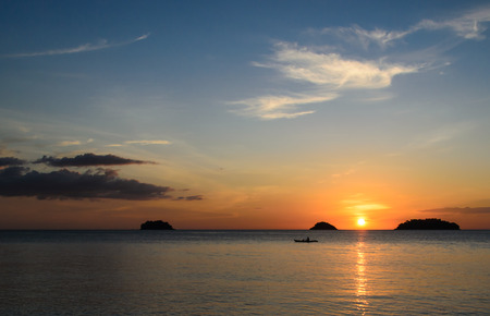 Kayakers silhouette on ocean during orange sunset photo