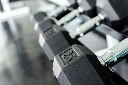 Close up rows of dumbbells on a rack in a gym photo