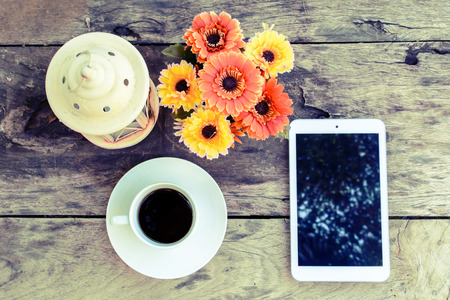 a cup of coffee and tablet on wood floor with flower, vintage style photo