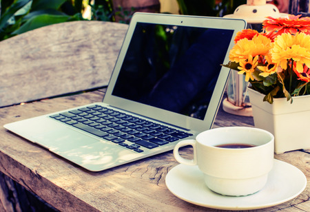 a cup of coffee and laptop on wood floor with flower, vintage style photo