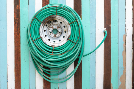 water hose hanging on vintage wooden  background photo