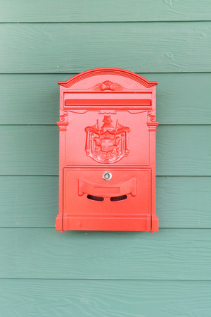 Red mailbox with green wood background photo