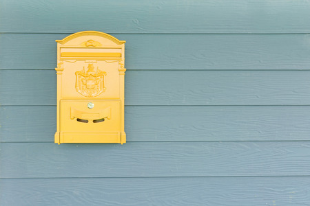 Yellow mailbox with green wood background photo