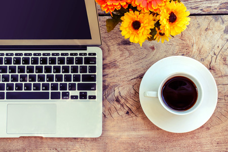 computer equipment: Cup of coffee and laptop on wooden table, vintage style Stock Photo