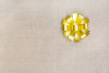 gloden: Gold ribbon on sackcloth background with copy space