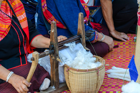 craftwork: Woman spinning cotton with a spinning wheel in Thailand Stock Photo