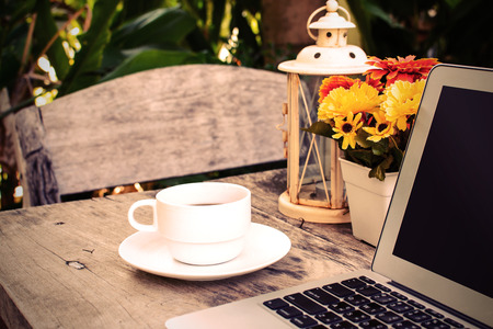a cup of coffee and laptop on wooden table with flower photo