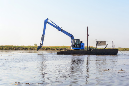 heavy duty, industrial excavator working in the river construction site photo