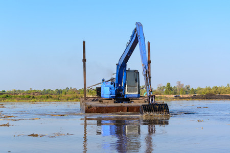 heavy duty, industrial excavator working in the river construction site Stock Photo