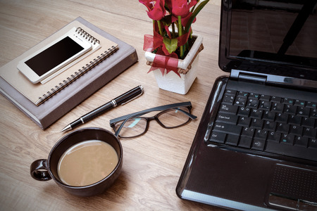 Laptop and cup of coffee with flower on desk, Vintage style photo