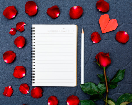 Red rose and petals with heart shape paper and notebook on black stone background photo