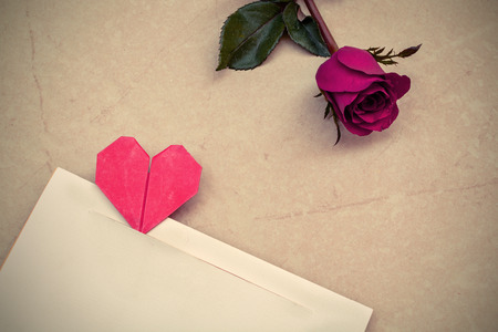Red rose and petals with heart shape paper on stone background photo