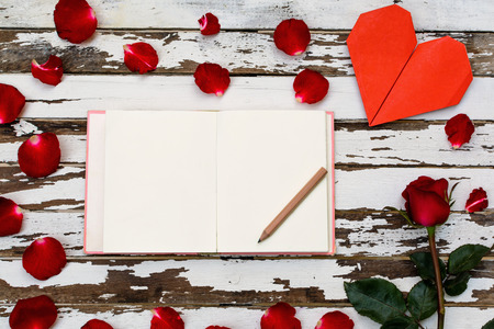 Red rose and petals with heart shape paper and notebook on wooden table photo