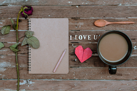 i love u: Cup of coffee and Withered rose, red heart shape, notebook on old wooden background Stock Photo