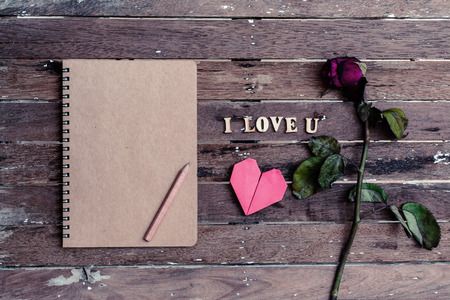 Withered rose and red heart shape and notebook on wooden background, Vintage style photo