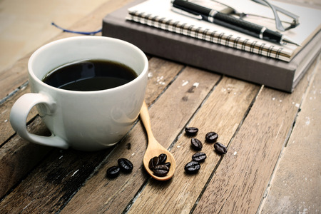 earpiece: Cup of coffee and beans with notebook, Soft light filter, Vintage style Stock Photo