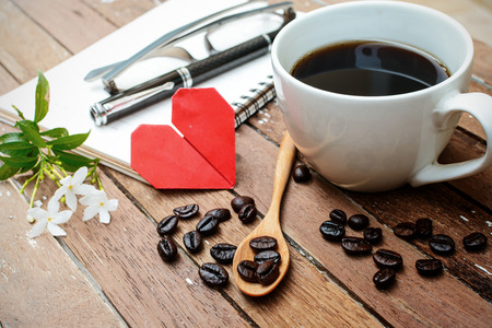 Cup of coffee and beans with notebook, flower, red heart shape and soft light, Vintage style photo