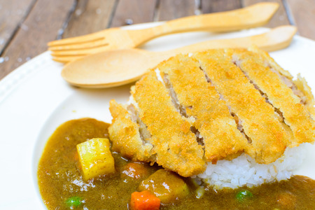 japanese curry and tonkatsu with rice on wooden table photo