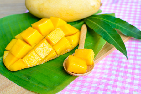spoon yellow: Fresh yellow mango with spoon on wooden table Stock Photo
