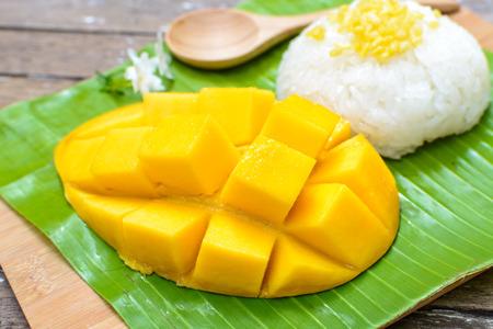 mango fruta: Close up de mango maduro y arroz pegajoso en mesa de madera Foto de archivo