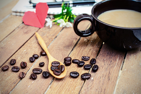 Cup of coffee and beans with notebook, flower, red heart shape photo