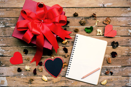 Blank notebook with red gift box on wooden table and heart shape photo