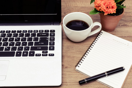 black and white flowers: Laptop and cup of coffee with flower on desk, Vintage style Stock Photo