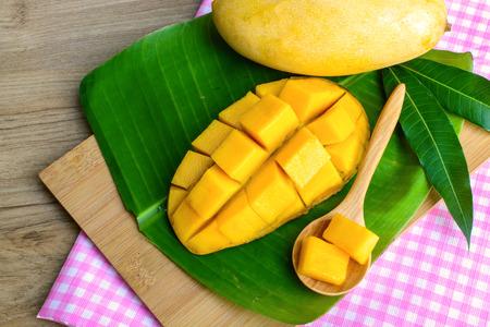 Fresh yellow mango with spoon on wooden table Zdjęcie Seryjne