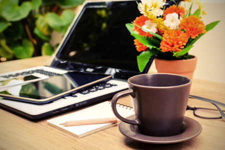 Laptop and cup of coffee with flower on desk, Vinatge style photo