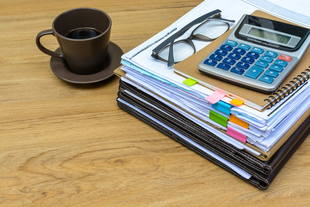 dossier: stack of folders and documents on office desk with coffee