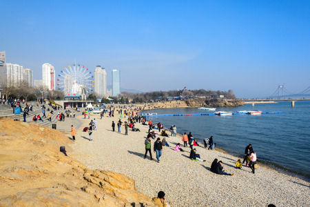 DALIAN, CHINA - March 15, 2015 : people relaxing at the beach at xinghai park