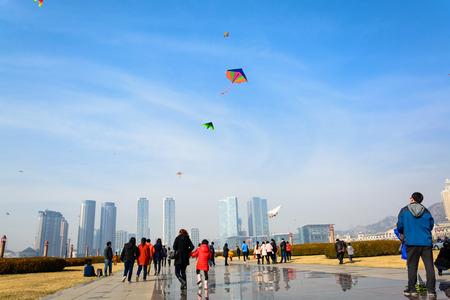 flying kites: DALIAN, CHINA - March 15, 2015 :  People flying kites at Xinghai square, Dalian China