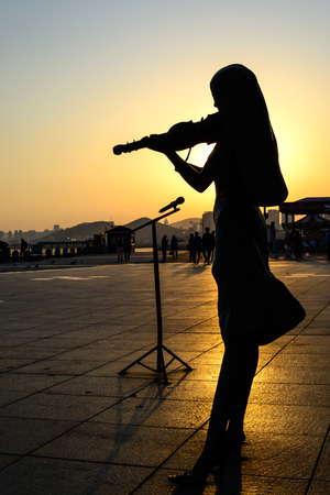 Silhouette of Girl playing the violin at sunrise photo