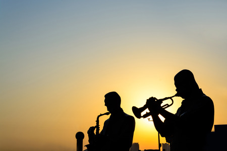 Silhouette of band playing the music at sunrise photo