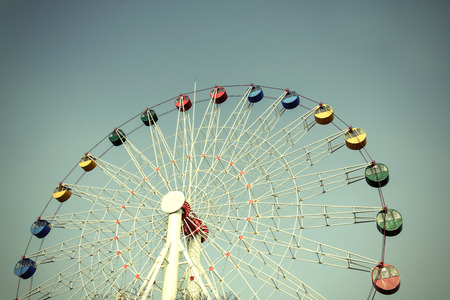 Colorful Giant ferris wheel against blue sky background, Vintage style photo