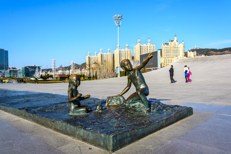 大連, 中国 - 2015 年 4 月 7 日: 少年と星海広場で少女の彫刻。正方形は、110 万平方メートルの総面積をカバーしています。