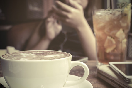 Cup of Coffee on wooden table in coffee shop, vintage style photo