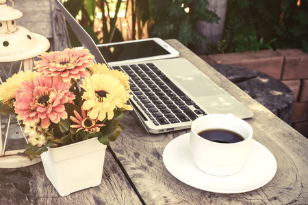 office break: a cup of coffee and laptop on wood floor with flower, vintage style