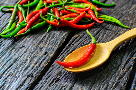 chili: Close up of chilli pepper in a spoon on wooden table