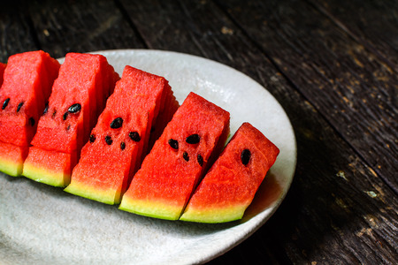 pulpy: slices of watermelon on wooden table with shadow