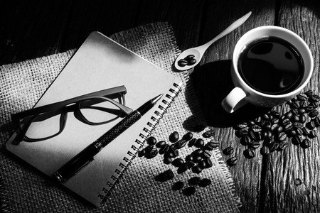 Cup of coffee and coffee beans with light and shadow on wooden table photo