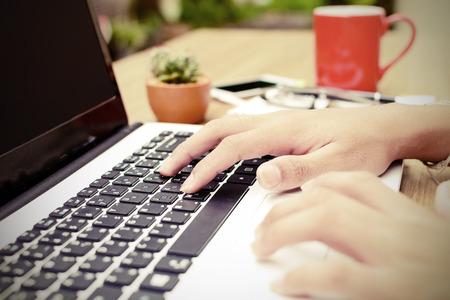 manos escribiendo en el teclado portátil en casa Foto de archivo