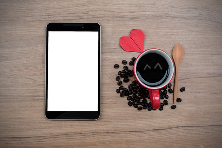 Cup of coffee with coffee beans and tablet on wooden table photo