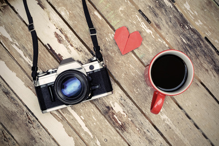 Cup of coffee with retro camera on old wooden table, Vintage style photo