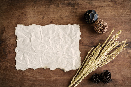 crinkled: old wrinkled paper on old wood background with dried flower Stock Photo