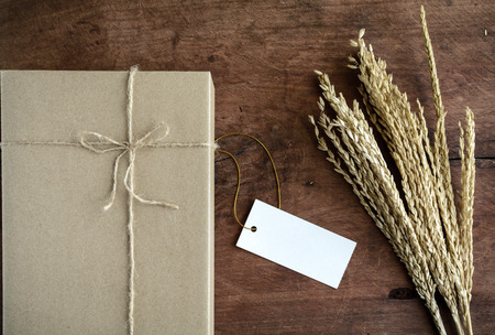 Brown paper box on old wood background with dried flower and copy space, Vintage tone photo