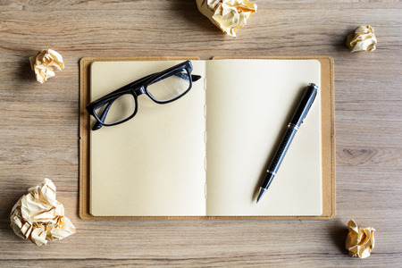Crumpled paper balls with eye glasses and notebook on wood desk, creative writing concept