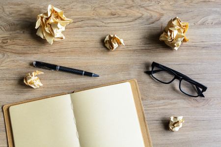 Crumpled paper balls with eye glasses and notebook on wood desk, creative writing concept photo